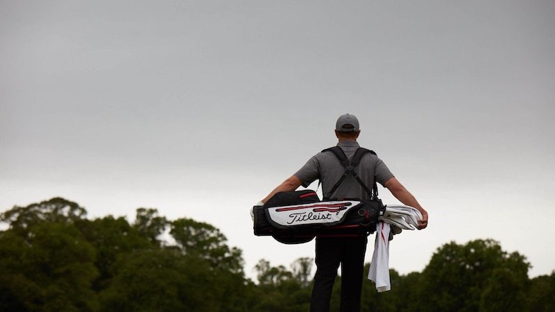 Golfer carrying a Titlest brand bag